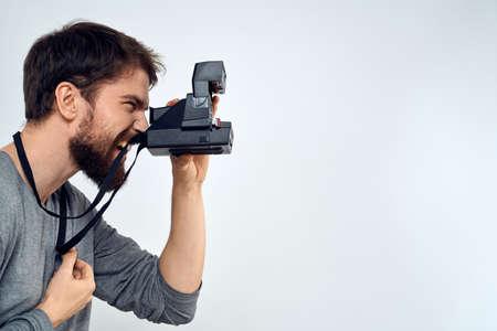 male photographer holding camera professional lens creative studio work light background