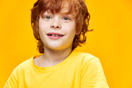 Funny red-haired boy front view yellow isolated background with an open mouth