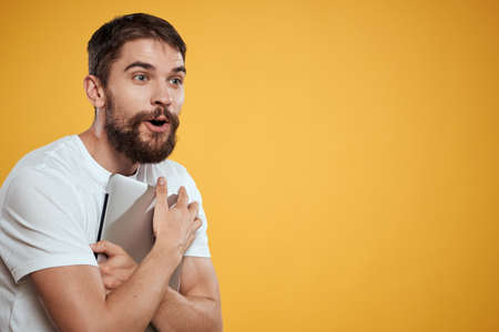 emotional man with laptop on yellow background gesturing with hands cropped view Copy Space