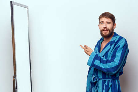 a man in a blue robe examines himself in a mirror in a bright room cropped view