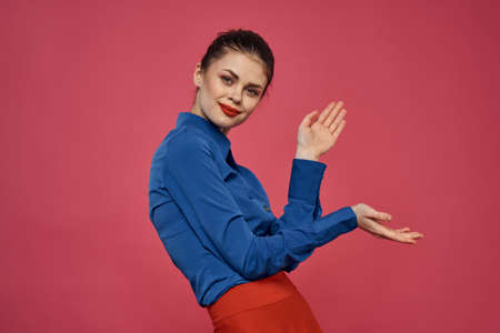 fashionable woman in blue shirt on pink background Red skirt emotions model gesturing with hands cropped view Copy Space