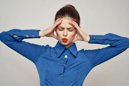 Portrait of a beautiful woman with red lips on a light background and a blue shirt cropped view 版權商用圖片