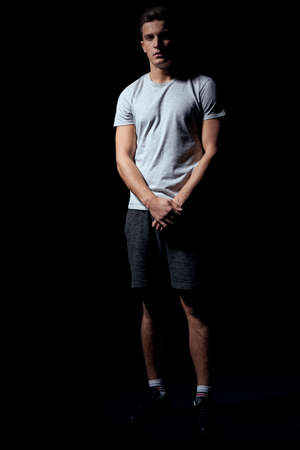 handsome man in a white t-shirt on a black background inflated arm muscles sport model Copy Space 写真素材