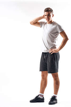 Athletic man on a light background in full growth and jogging charging shorts sneakers t-shirt