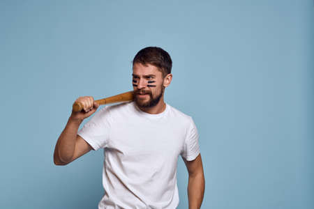 emotional man with a bat in his hand on a blue background and makeup on his face black lines energy t-shirt baseball