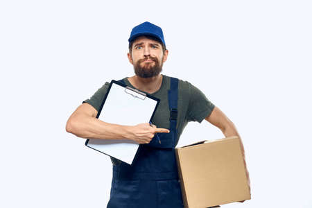 Man in working uniform box delivery loader courier light background
