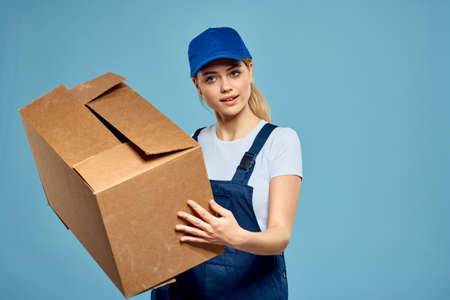 Woman working form box in hands packing delivery service blue background