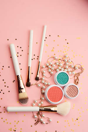 eyeshadow accessories beads makeup brushes collection professional cosmetics on pink background