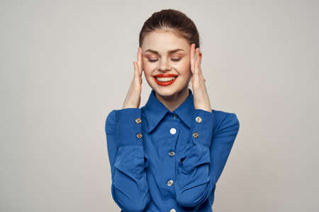 Portrait of a beautiful woman with red lips on a light background and a blue shirt cropped view