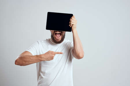 emotional man with a tablet in front of his eyes gesturing with his hands cropped view Copy Space Model light background