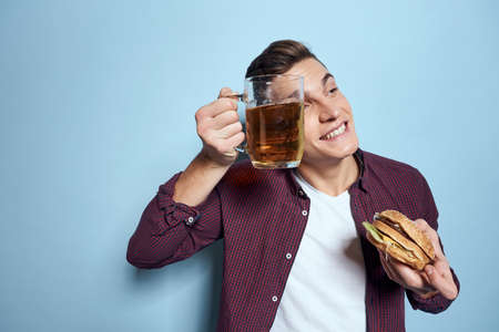 cheerful drunk man with beer mug and hamburger in hand diet food lifestyle blue background