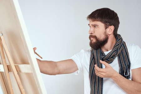 A man artist draws on an easel a scarf white t-shirt art hobby creativity Stock fotó