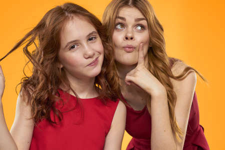 A red-haired girl and a beautiful woman on a yellow background in red dresses gesticulate with their hands and grimace Foto de archivo