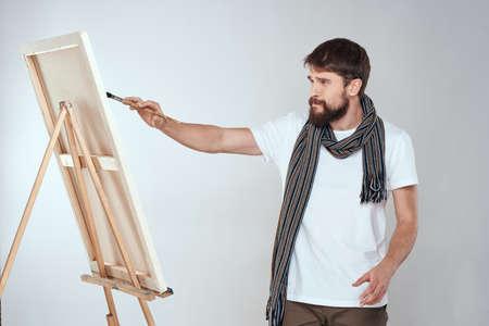 A man artist draws on an easel a scarf white t-shirt art hobby creativity