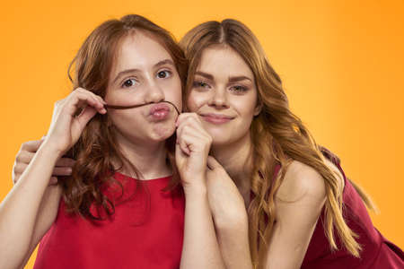 A red-haired girl and a beautiful woman on a yellow background in red dresses gesticulate with their hands and grimace