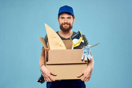 Worker man in uniform box tools construction blue background