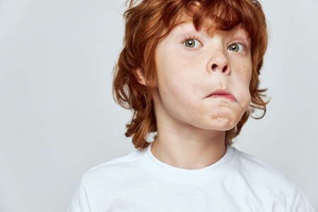 Grimacing red-haired child with puffed out cheek white t-shirt cropped