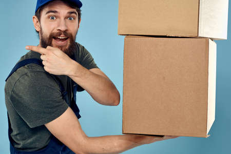 Man in working uniform with boxes in hands delivery service blue background 版權商用圖片