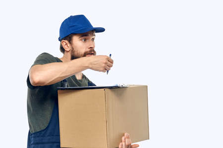 Working male courier with box in hand documents delivery service light background
