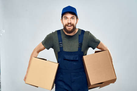 Man in working uniform with boxes in hands delivery loading lifestyle 版權商用圖片