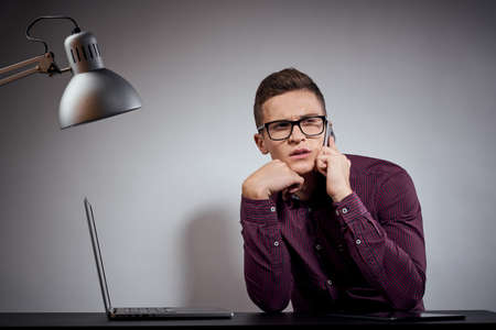 businessman in glasses and a shirt sits at a table with open laptops Coffee Space mobile phone 스톡 콘텐츠