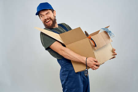 man in work uniform with box in hands tools lifestyle light background 版權商用圖片