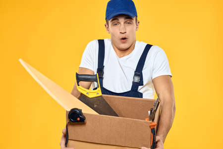 worker with box in hand tools loader yellow background 版權商用圖片