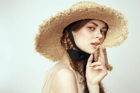 cute girl in straw hat with black ribbon and dress on beige background cropped view