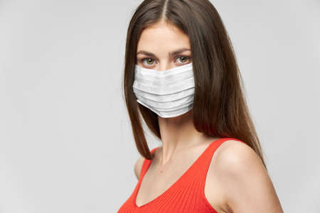 Woman in a medical mask and Red T-shirt look ahead