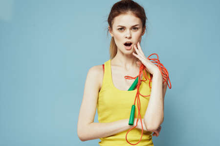 Woman with skipping rope sport exercise yellow tank top blue background
