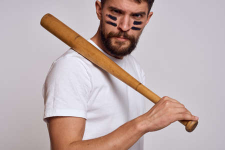 An emotional man with a baseball bat on a light background in a white T-shirt is gesturing with his hands to the model