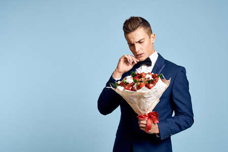 romantic man with a bouquet of flowers and in a bow tie on a blue background cropped view