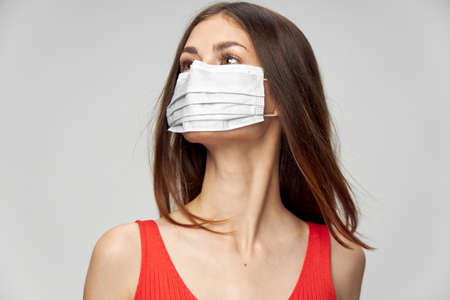 Woman in medical mask red tank top looks to the side light background studio