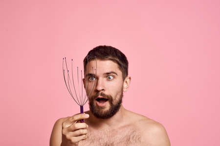 man with head massager relax body care pink background