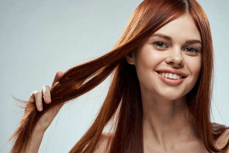 pretty redhead woman holding her hair with hands grooming naked shoulders light background