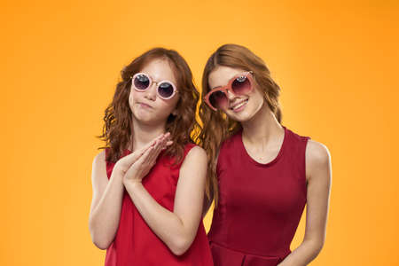 Happy sisters in red dresses on a yellow background are having fun and gesticulating Copy Space