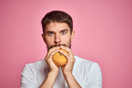 Young man with orange on a pink background in a white t-shirt emotions fun gesticulating with model hands Imagens