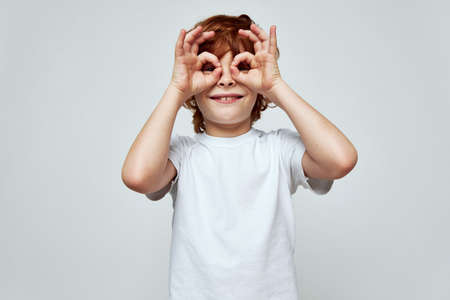 cheerful smiling redhead boy holding his hands near his eyes in the form of a mask white t-shirt