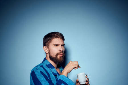 man in striped blue robe holding white cup in hand and emotions fun surprise model cropped view 免版税图像 - 157233197