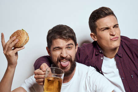 Two friends drink beer leisure fun alcohol friendship lifestyle light background