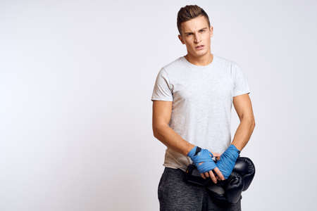 Strong man with boxing gloves and in a white t-shirt on an isolated background cropped view of the model