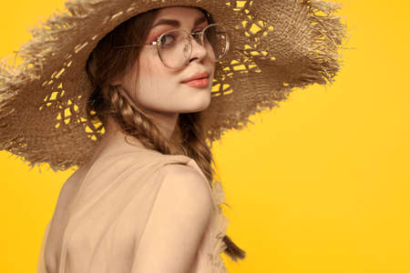 Portrait of a pretty woman with pigtails and with a hat on her head on a yellow background cropped view Archivio Fotografico