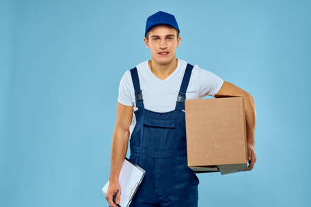 Man worker with cardboard box delivery loader lifestyle blue background