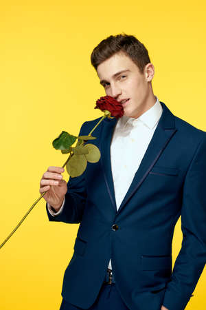 Gentlemen in classic suit on yellow background and red rose romance cropped view model portrait.