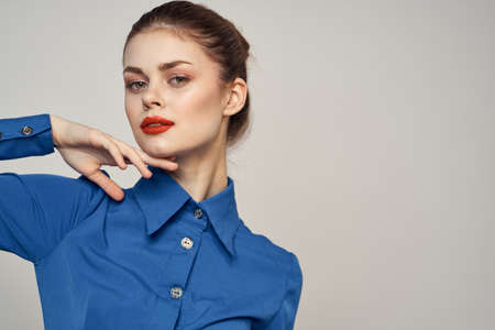 Portrait of a beautiful woman with red lips on a light background and a blue shirt cropped view. High quality photo