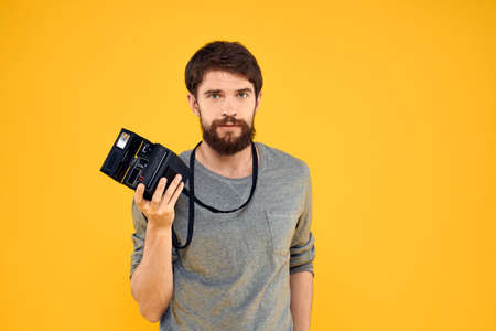 Male photographer with professional photo camera. Professional Creative approach studio yellow background