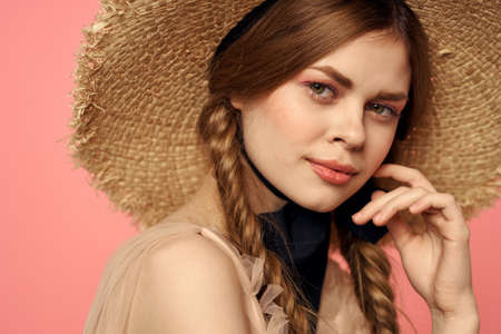 Portrait of a girl in a straw hat on a pink background emotions close-up beautiful face model pigtails Stockfoto