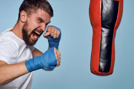 a man practicing a punch on a punching bag in a white t-shirt on a blue background Stockfoto