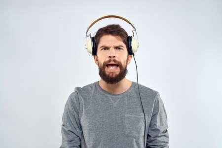 Man in headphones listens to music lifestyle modern style technology light background Stockfoto