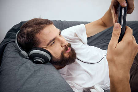A man lies on the couch with gamepad headphones playing leisure lifestyle Stockfoto